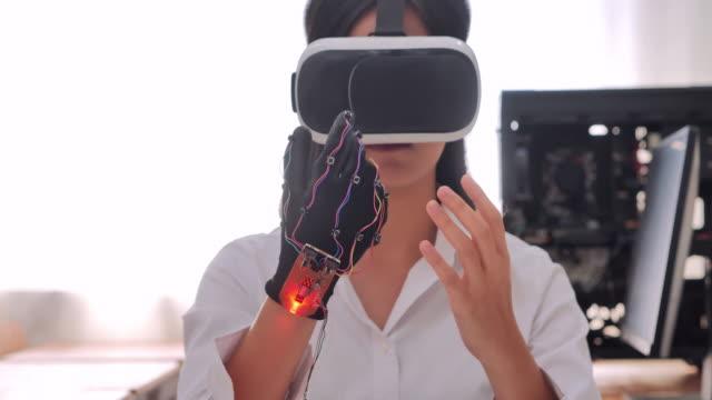 genç kız sanal gerçeklik kulaklık giyen ve masada masasında otururken ve atölyede hackathon çalışırken gesturing. i̇novasyon, eğitim, teknoloji, bilim, i̇nsan kavramı. eğitim konuları.endüstri 4.0.stem'de kadınlar - sanal gerçeklik stok videoları ve detay görüntü çekimi