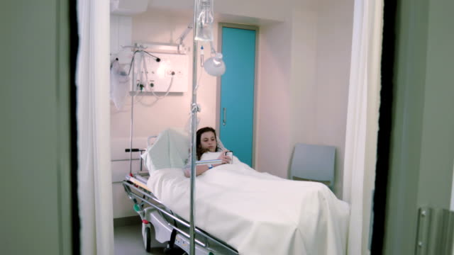 Teenage girl with a phone in the hospital ward video