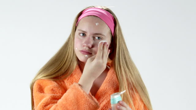 Teenage girl with a problem face skin applying cleansing skincare lotion video