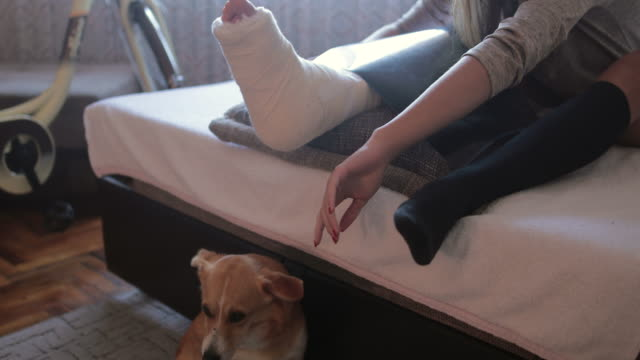 Teenage girl with broken leg cuddling her dog at home