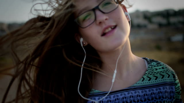 Teenage girl with eyeglasses listening to the music and singing outdoor video