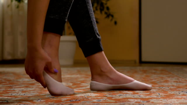 Teenage girl with flats rubbing her tired sole foot muscles relaxing her leg video
