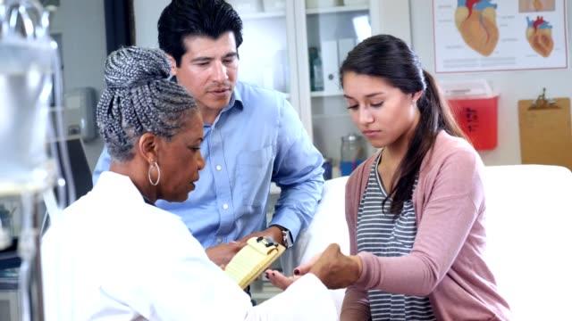 vídeos de stock, filmes e b-roll de adolescente com pulso lesionado fala com o médico de emergência - punho