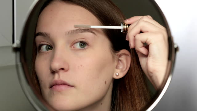 Teenage girl, with moles on the face, combing her eyebrows. video