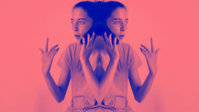 Teenage girl with yellow T-shirt talking on the mobile phone. Mirror effect on due tone