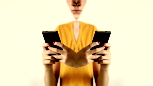 Teenage girl with yellow T-shirt texting on the mobile phone. Mirror effect