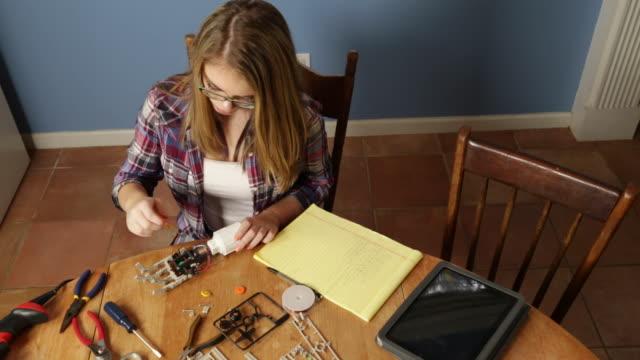 adolescente ragazza lavorando su un progetto di robotica - stelo video stock e b–roll