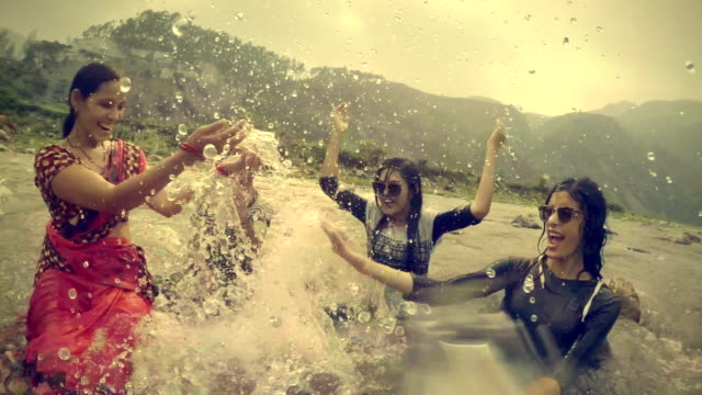 Teenage girls doing fun and enjoying in river with family. Outdoor slow motion video of happy, Asian, teenage and young adult girls enjoying their summer vacation with their mother and sister and doing fun in a river in mountain by splashing cold water of the river on each other. indian family stock videos & royalty-free footage