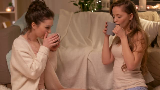 vídeos de stock e filmes b-roll de teenage girls drinking hot chocolate with marshmallow at home - hygge