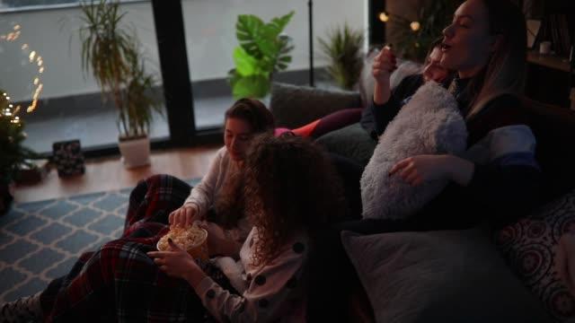 Teenage girls eating popcorns and watching movie