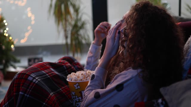 vidéos et rushes de adolescentes manger pop-corn et regarder film - regarder attentivement