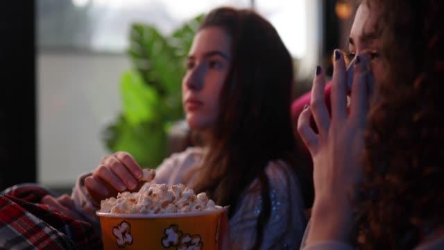 teenage girls eating popcorns and watching movie - christmas movie video stock e b–roll