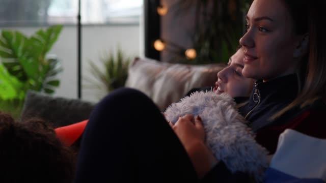 ragazze adolescenti che mangiano popcorn e guardano film - christmas movie video stock e b–roll