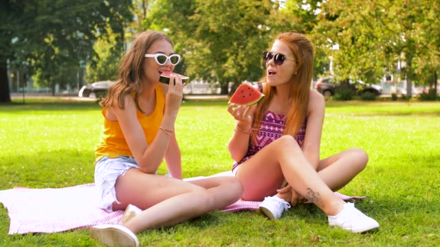 teenage girls eating watermelon at picnic in park leisure and friendship concept - happy smiling teenage girls or friends eating watermelon at picnic in summer park watermelon stock videos & royalty-free footage