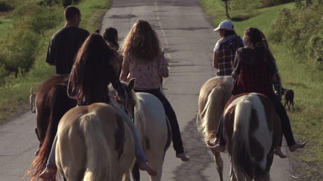 teenage girls group riding horses on country dirt road super slow motion - ekoturystyka filmów i materiałów b-roll