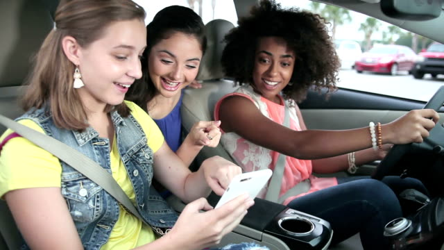 teenage girls in car looking at mobile phone, talking - tre persone video stock e b–roll