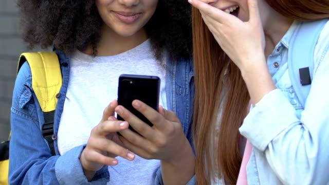 stockvideo's en b-roll-footage met tiener meisjes lachen op social media berichten over klasgenoten, cyberpesten - kids online abuse