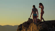 istock Teenage girls on a high cliff diving into the Adriatic Sea at sunset 1285626635
