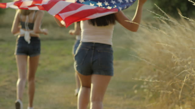 Teenage girls running with American Flag celebrating Independence Day video