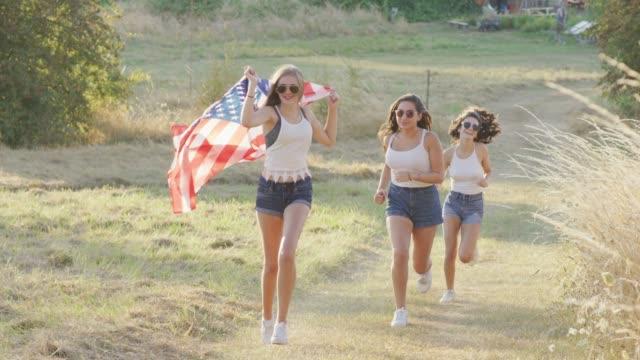vidéos et rushes de adolescentes en cours d'exécution avec un drapeau américain - patriotisme