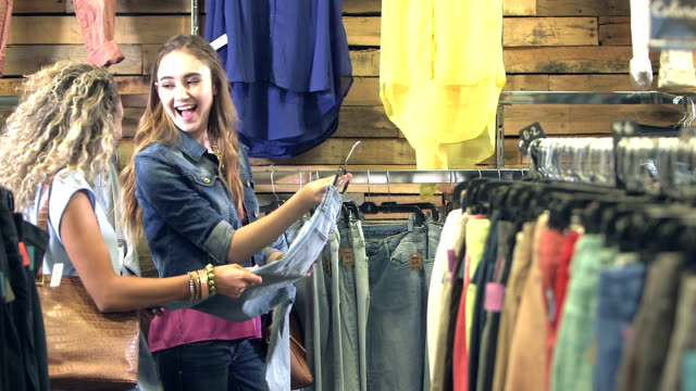 Teenage girls shopping for jeans in clothing store video