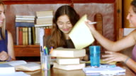 istock Teenage girls take a break from studying by throwing paper - dolly shot 1201807296