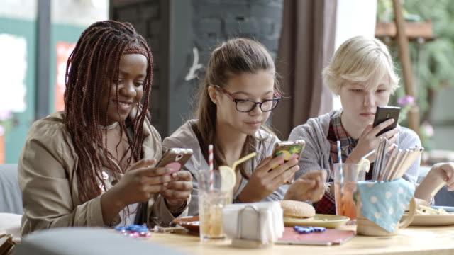 Teenage Girls Texting on Smartphones in Outdoor Cafe