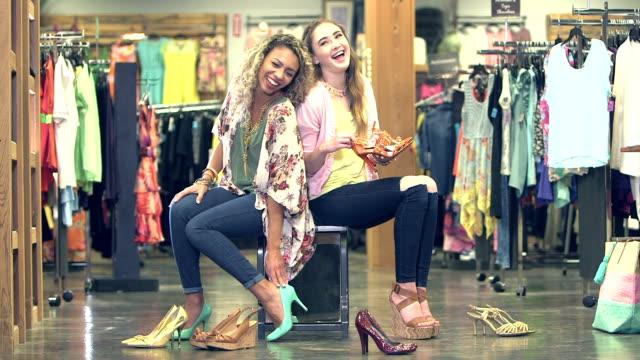 vídeos de stock, filmes e b-roll de garotas adolescentes experimenta sapatos em loja de roupas - shopping center