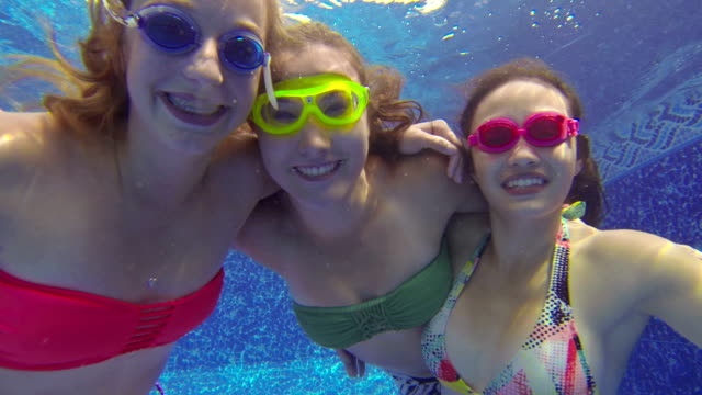 Teenage girls with goggles looking underwater video