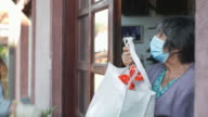 istock Teenage girl,volunteer,delivering groceries to a senior woman, insulation,COVID 19 1220768645