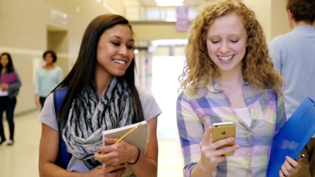 Teenage high school girls laughing and using smart phone in busy hallway video