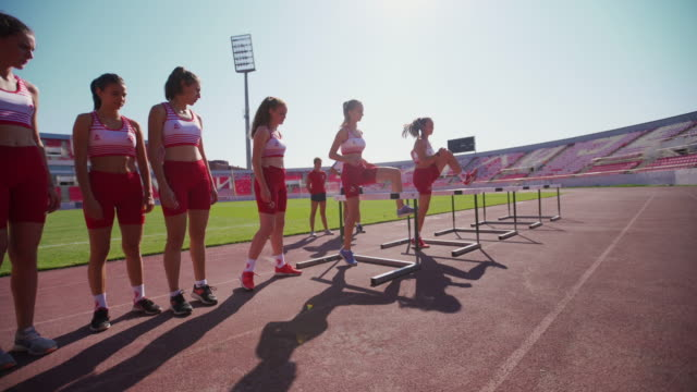 vídeos y material grabado en eventos de stock de corredores adolescentes saltando obstáculos en la pista - valla artículos deportivos