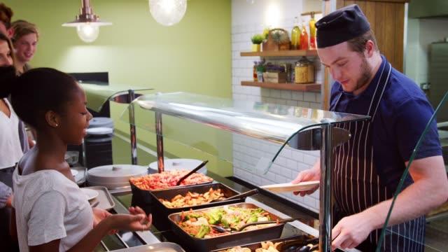 teenage students being served meal in school canteen - stołówka filmów i materiałów b-roll