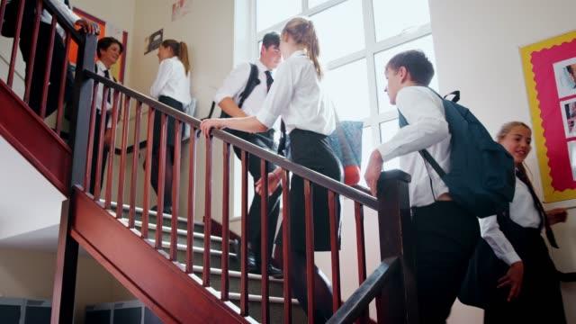vídeos de stock, filmes e b-roll de estudantes adolescentes em uniforme ao descer escadas entre aulas - reino unido