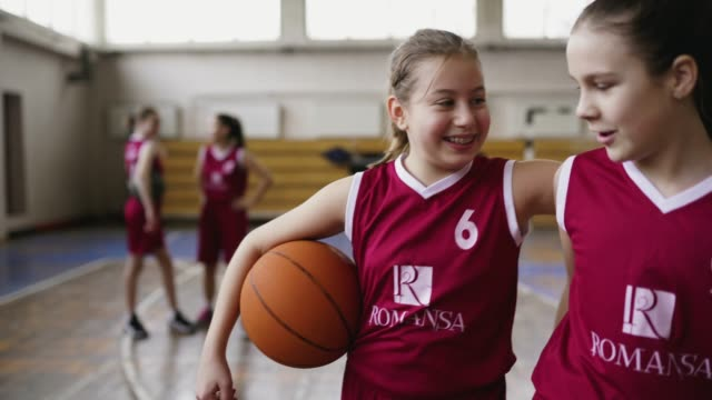 Teenage teammates embracing Cheerful teenage girls embracing after training, while walking and holding basketball ball, smiling lively indoor match sport stock videos & royalty-free footage