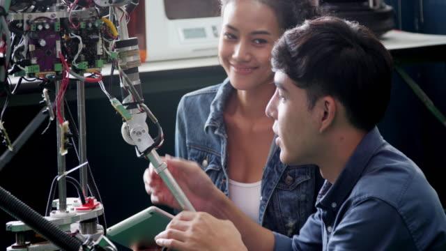 vídeos y material grabado en eventos de stock de adolescente trabaja en un robot programable totalmente funcional para el proyecto de club de robótica de la escuela. diseñador creativo pruebas prototipo de robótica en taller. concepto de ciencia - 20 a 29 años