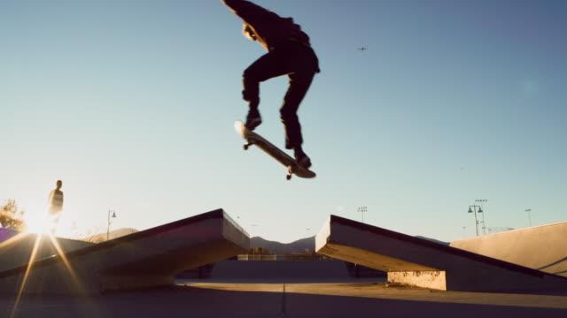 十代の白人少年がスケートパークで彼のスケート ボードを定期的に足オリー オーバー ギャップを実行します。 - エクストリームスポーツ点の映像素材/bロール