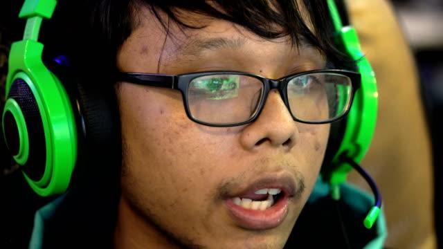 CU Teenager Asian boy gamer wearing green headset playing computer video game video