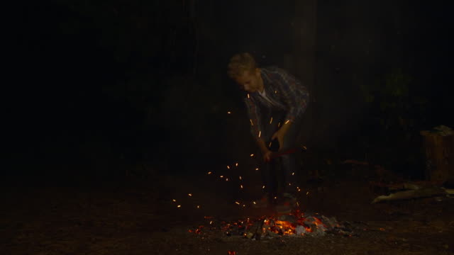 Teenager boy beating hot coals with wooden stick in fire with sparks in campsite. Hiker boy tedding coals in cooled bonfire in dark forest at camping. Teenager boy beating hot coals with wooden stick in fire with sparks in campsite. Hiker boy tedding coals in cooled bonfire in dark forest at camping stamping feet stock videos & royalty-free footage