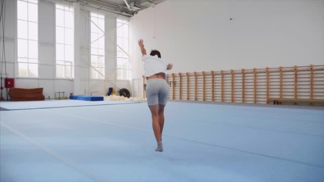 vídeos de stock, filmes e b-roll de um menino do adolescente está fazendo um cartwheel e uma aleta traseira tripla na ginástica, steadicam. - ginástica