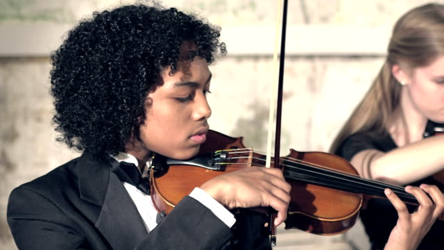 Teenager boy playing violin in concert video