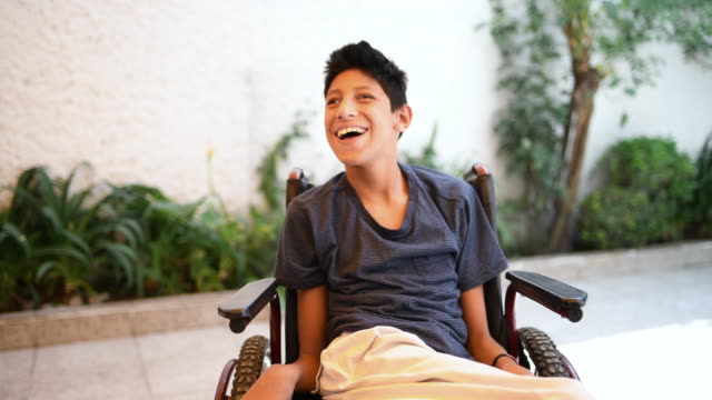 Teenager boy with Cerebral Palsy Real time video portrait of teenager boy with Cerebral Palsy on wheelchair disability stock videos & royalty-free footage