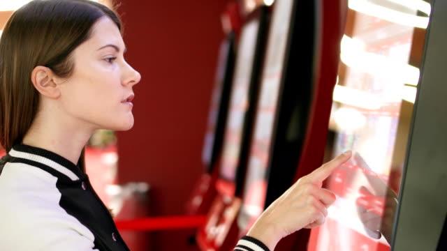 ティーンエイ ジャー映画で自販機から映画のチケットを購入します。画面に触れることによって女性をジェスチャー - タッチスクリーン点の映像素材/bロール