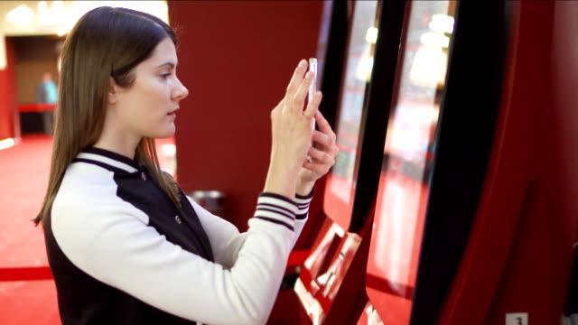 ティーンエイ ジャー映画で自販機から映画のチケットを購入します。女性の携帯電話、写真を使用して - タッチスクリーン点の映像素材/bロール
