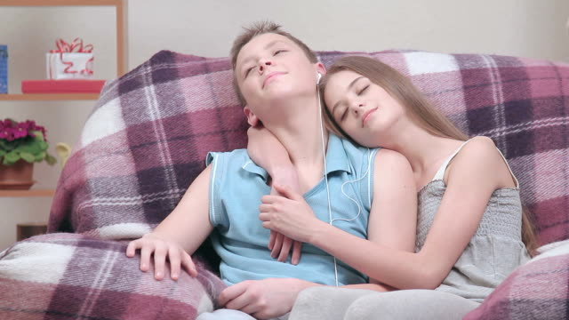 Teenager couple resting indoors, boy listening to music through headphones video