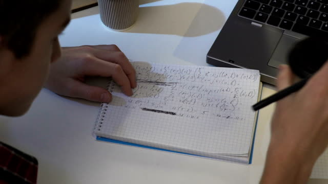 Teenager drinking energetic tea while doing homework, school test preparation video