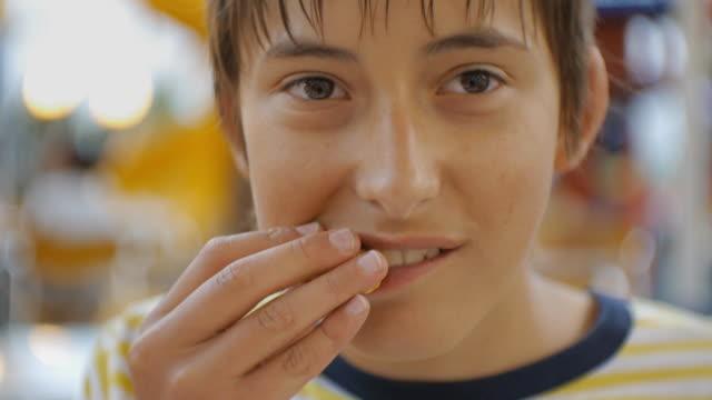 패스트 푸드를 먹는 대. 백인 십 대의 소년 물고 씹는 된다고 야외에서의 근접 샷. - burger and chicken 스톡 비디오 및 b-롤 화면