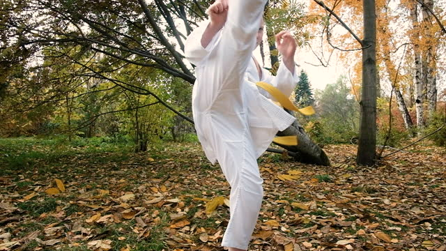 teenager girl 12 years old is engaged in karate outdoors in the park. Healthy lifestyle concept. playing sports. martial arts. Judo, Jiujitsu. brave, strong