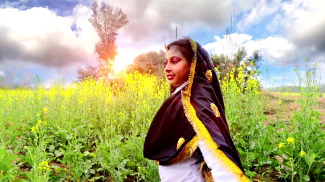 Teenager girl dancing near mustard crop field video