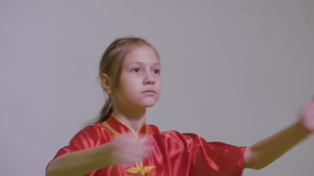 Teenager girl do kung fu greeting two hands together with right fist on the left palm is the Wushu Tai Chi Chinese Martial Art greeting. Fist and palm salute. Salutation in Kung Fu